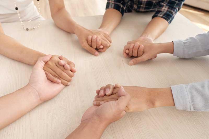 Quattro persone si tengono per mano non riconoscibili